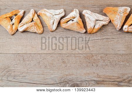 Hamantaschen cookies for Jewish festival of Purim on wooden background