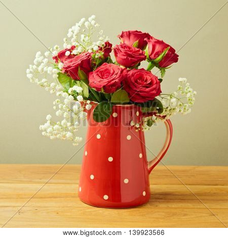 Red roses in polka dots jug on wooden table