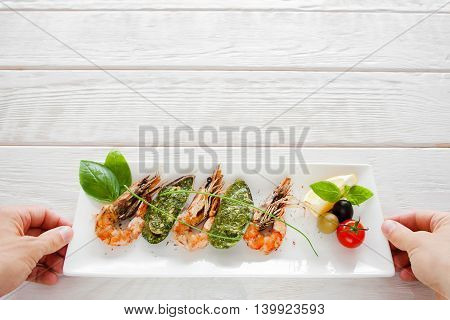 Mediterranean exotic seafood serving, copyspace. Hands put plate with cooked shrimp and mussels on white wooden background