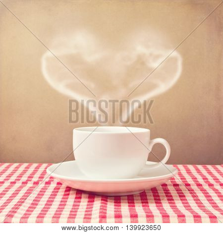 Coffee cup with heart shape steam over grunge background