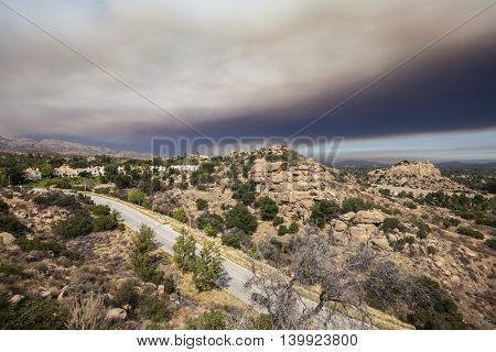 Brush fire smoke sky over the suburban edge of Los Angeles, California.