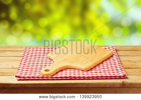 Cutting board on tablecloth on wooden table over bokeh garden background