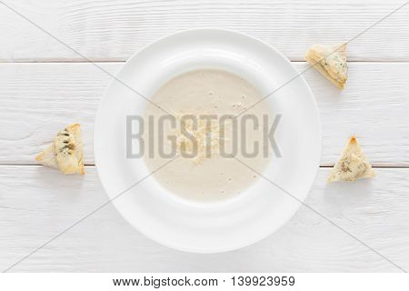Cheese soup-puree with canape on white wooden background, flat lay. Homemade organic cream-soup with bruschetta slices