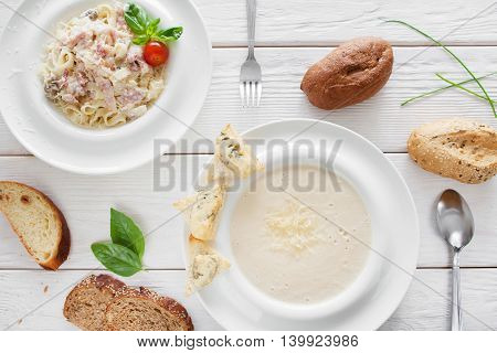 Traditional italian dinner in restaurant, flat lay. Cheese cream-soup and spaghetti carbonara served with bread on white wooden background. European cuisine concept