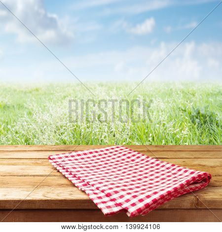 Wooden table with checked tablecloth over meadow