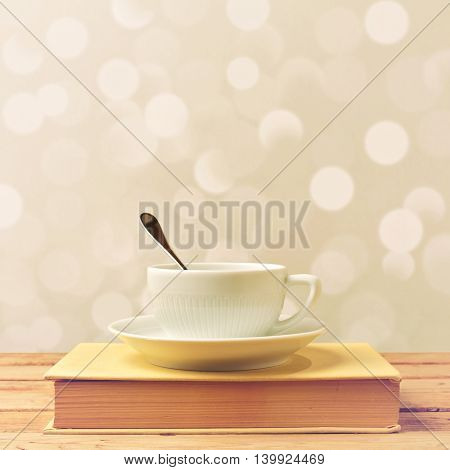 Coffee cup on book on wooden table over bokeh background