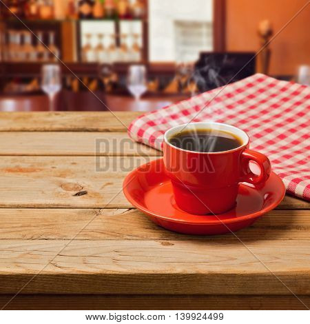 Coffee cup with checked tablecloth on wooden table