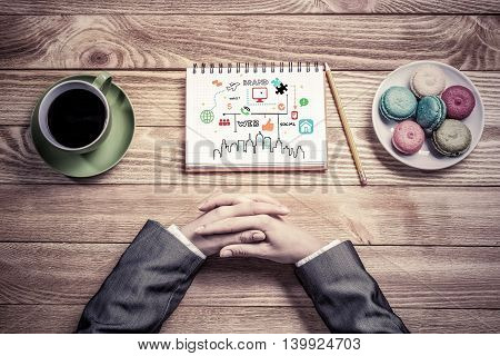 Top view of female hands folded on table and business sketches in notepad