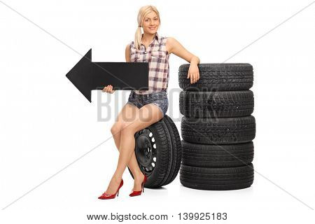 Female mechanic sitting by a pile of tires and holding a black arrow pointing left isolated on white background