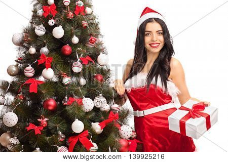 Female Santa standing by a Christmas tree and holding present isolated on white background