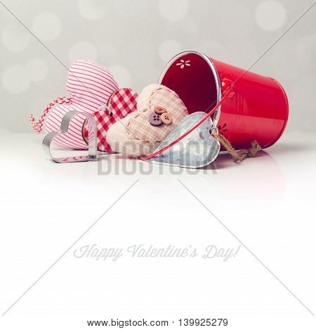 Valentine's day background with heart shapes and bucket over white