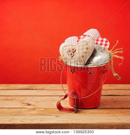 Valentine's day heart shapes in bucket on wooden table