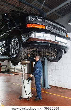 Change engine oil and transmission inspection in SUV. Car on the lift in garage, working mechanic under vehicle