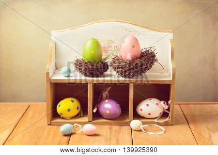 Easter eggs decorations on wooden table over retro background