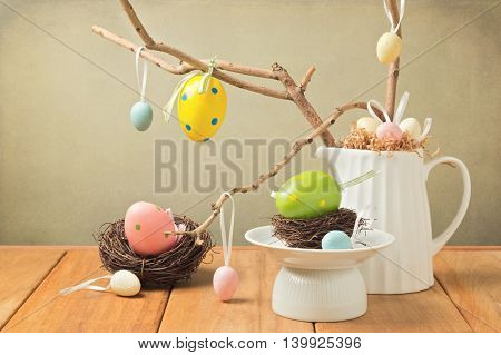 Easter eggs decorations with branches and bird nest on wooden table