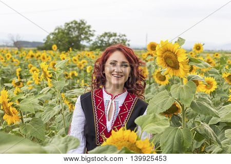 Girl in a traditional Bulgarian dress feeling happy in a field of sunflowers
