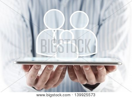Hands of businessman holding tablet pc and family concept on screen