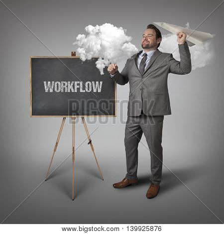 Workflow text on blackboard with businessman and paper plane
