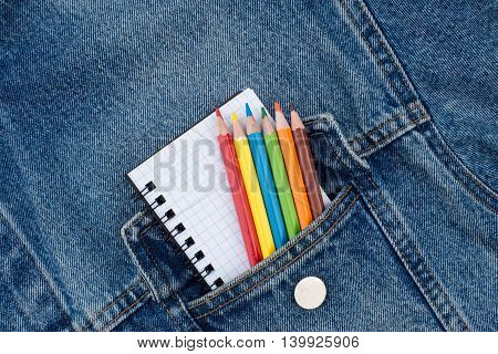 Pocket denim jacket with a notebook and colored pencils. Top view