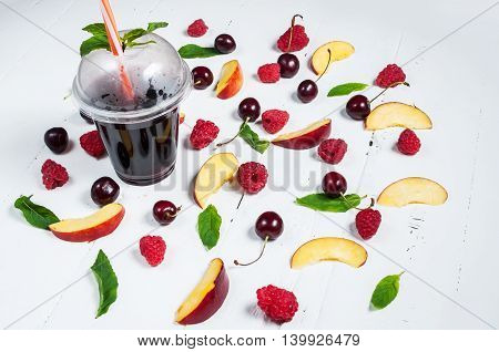 Various types of fruits with green leaves and frozen cocktail berries on white wood background.