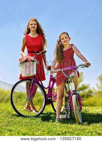Bikes bicycle girl. Teenager girl and child wearing red polka dots dress keeps bicycle with flowers basket. Summer outdoor in park. aganist blue sky.