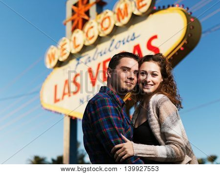 happy couple posing in front of welcome to las vegas sign together