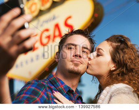 happy couple take selfie in front of the welcome to las vegas sign