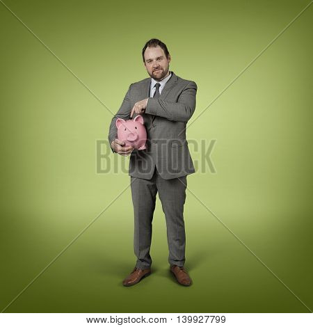 Businessman holding piggy bank with blank background