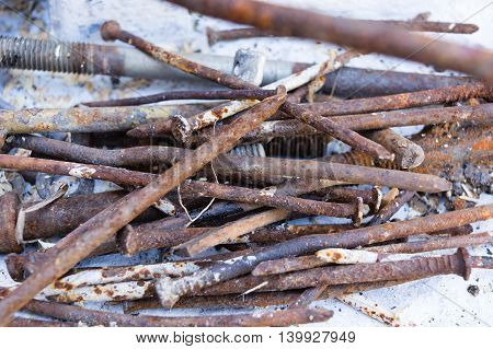 heap of iron rusty nails and fasteners on a white background