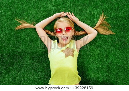 Cheerful little girl in colorful clothes and sunglasses lying on a green lawn. Kid's fashion. Summer holidays.