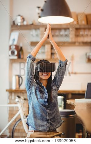 Young woman using the virtual reality headset for performing yoga at office cafeteria