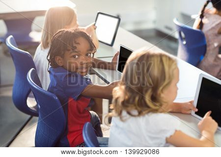 Portrait of smiling boy with classmates using digital tablet in classroom