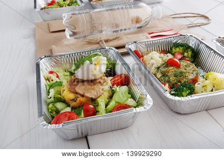 Healthy food restaurant delivery and diet concept. Take away of fitness meal. Weight loss lunch in foil boxes. Poached egg with steak, paper bag, water bottle and other dishes at white wood