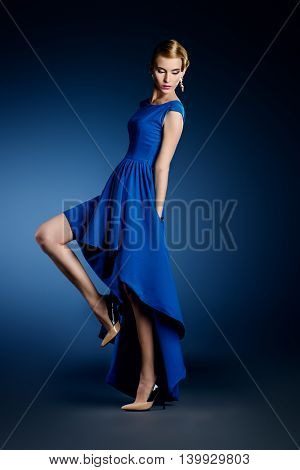 Fashion portrait of a beautiful young woman in  elegant evening dress posing in motion at studio. Hairstyle.