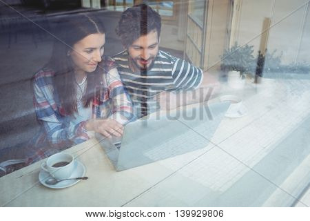 Young couple using laptop with coffee at cafe