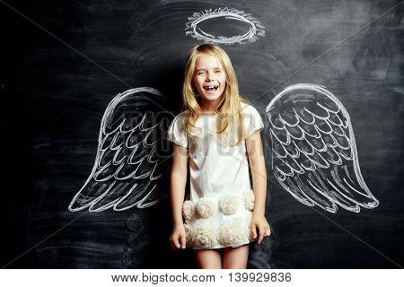 Pretty little angel girl. Cute child girl posing with angel wings drawn on a blackboard.