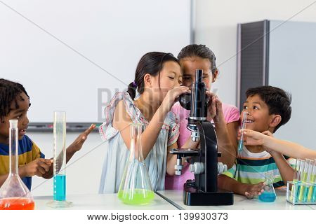 Schoolchildren looking in microscope in lab