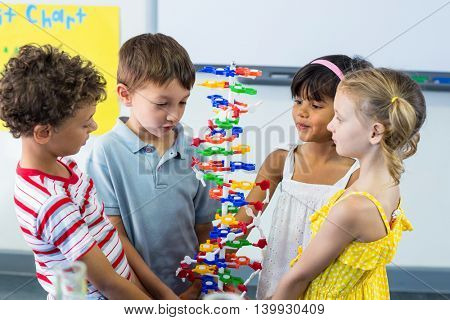 Cute schoolchildren holding DNA model in classroom