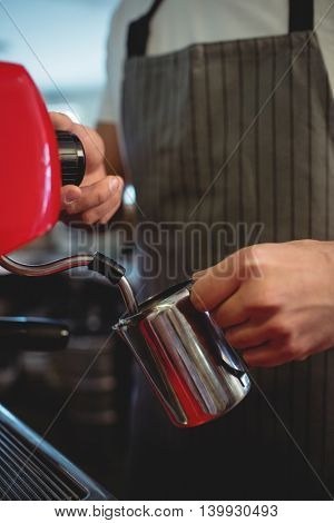Midsection of male barista pouring coffee from espresso maker at cafe
