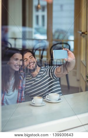 Cheerful young couple taking selfie from cellphone at cafe