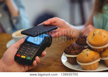 Cropped image of male barista and female customers using technologies at cafe