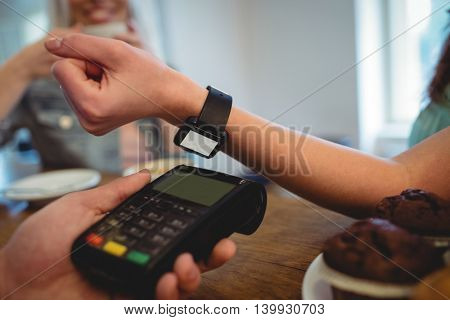 Cropped image of female customer with smart watch at cafe