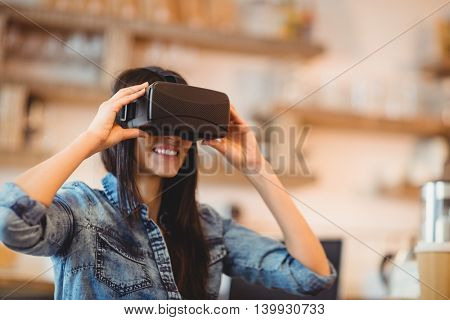 Young woman using the virtual reality headset at office cafeteria
