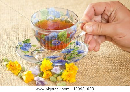 full glass mug of tea with yellow and blue flowers