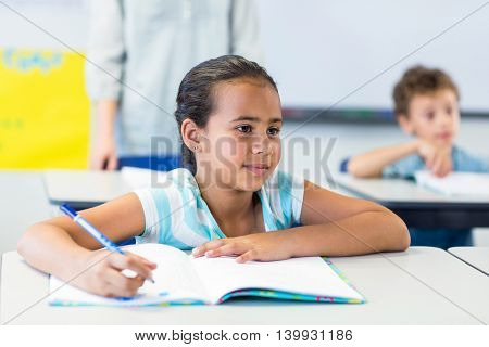Smiling girl writing on book in classroom