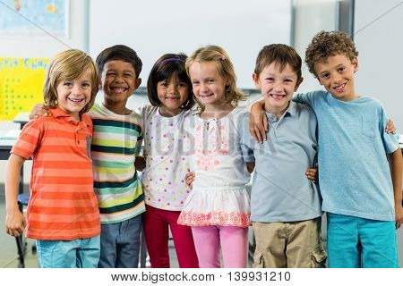 Portrait of happy schoolchildren standing in classroom