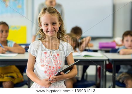 Portrait of cute girl holding digital tablet in classroom