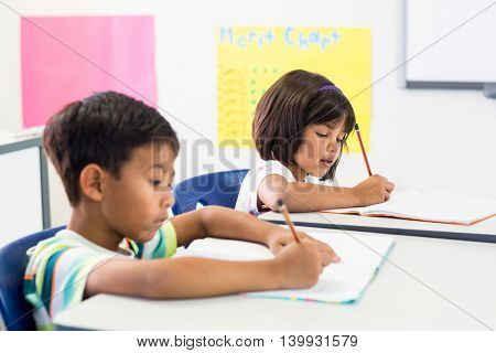 Cute schoolchildren writing on books in classroom