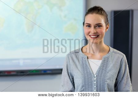 Portrait of smiling female teacher standing against projector screen in classroom