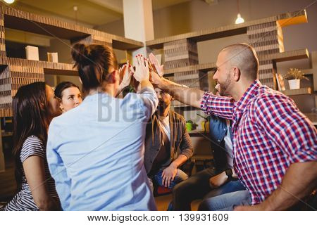 Colleagues giving high five during meeting at office